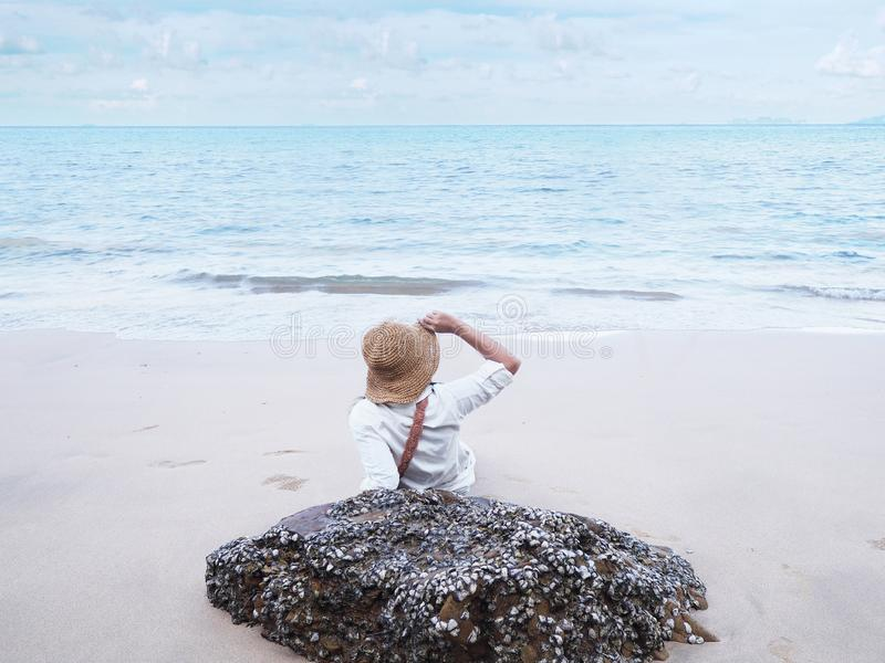 Back view of happy young woman sitting on sand and looking to the ocean royalty free stock photography