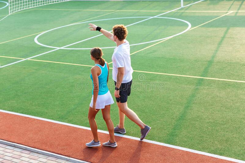 Back view of a healthy fitness couple walking at the stadium royalty free stock photos