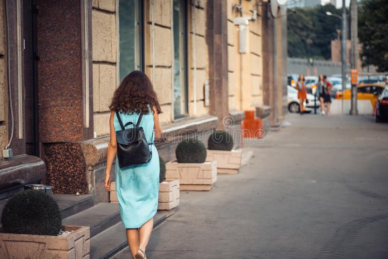 Back view of a hipster girl in a blue dress with black leather backpack walking on city street royalty free stock photo