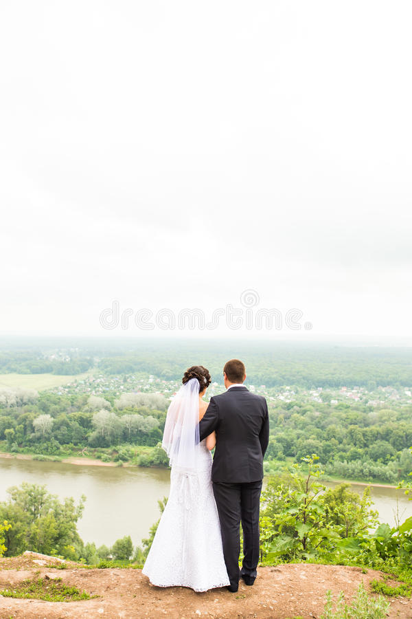Back view of holding hands bride and groom outdoors stock photography