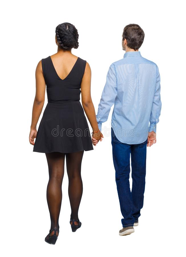 Back view of interracial going couple. walking friendly girl and stock photos