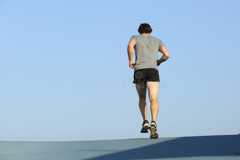 Back view of a jogger man running against blue sky stock images