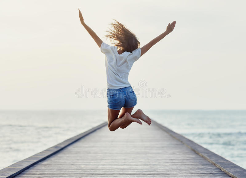 Back view of jumping girl on the pier royalty free stock photo
