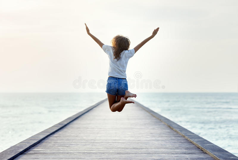 Back view of jumping girl on the pier stock image
