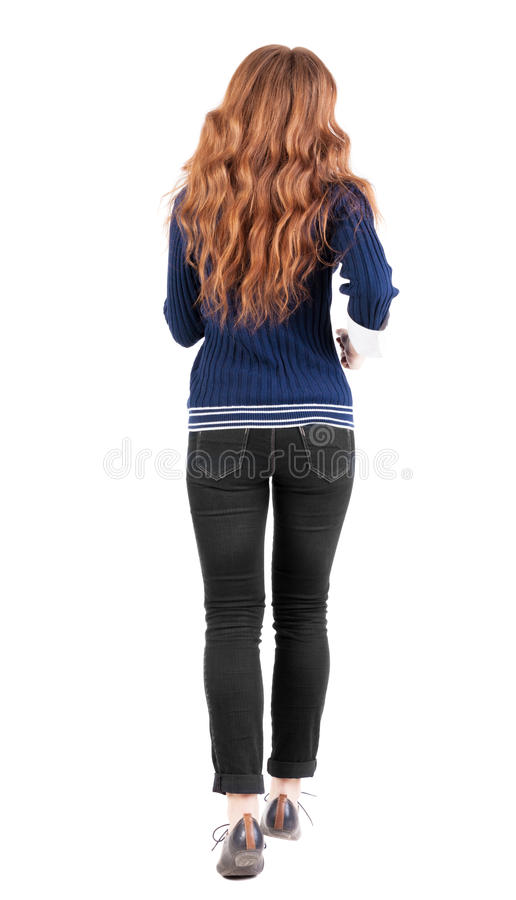 Back view of jumping woman in jeans. Beautiful redhead girl in motion. girl running quickly. backside view of person. Rear view people collection. Isolated stock photography