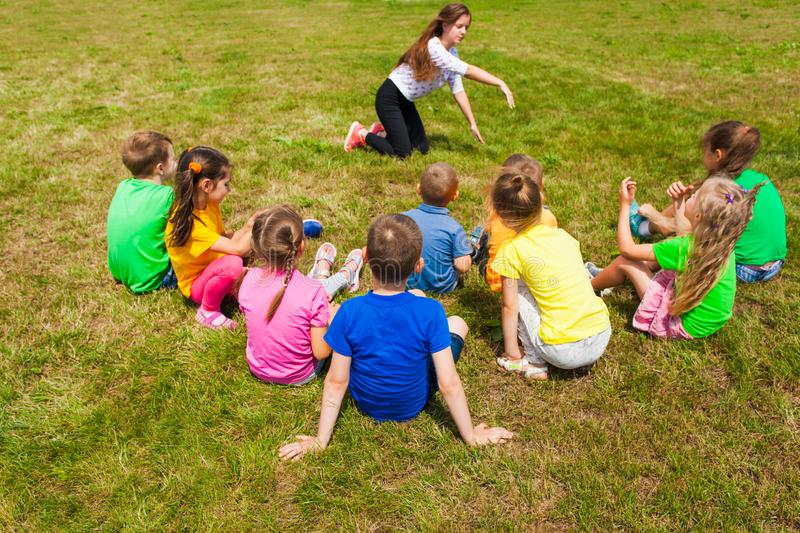 Back view of kids sitting on a grass playing charades stock photography