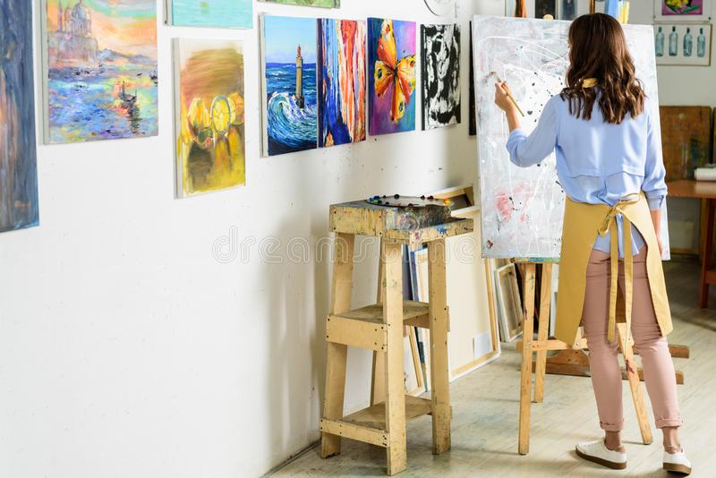 Back view of left-handed female artist painting on canvas. In workshop royalty free stock photography