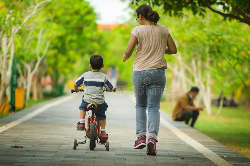 Back view lifestyle portrait of mother and young happy son at city park having fun together the kid learning bike riding and the royalty free stock images