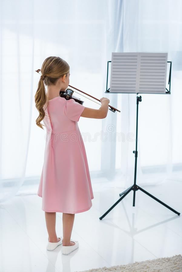 Back view of little child in pink dress playing violin. At home stock images