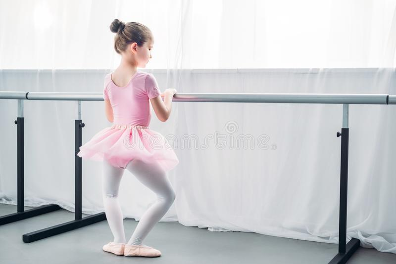 Back view of little child in pink tutu practicing ballet in ballet school stock images