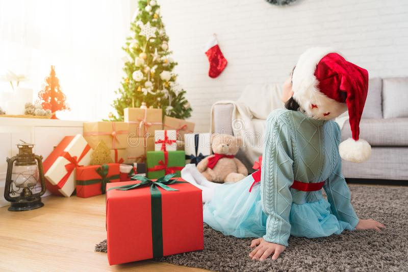 Back view of a little cute girl sitting on the floor. Of living room with her big gift box face to decorate Christmas tree at home royalty free stock images