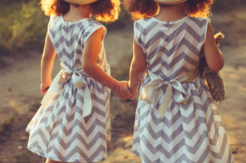 Back view of little girls sisters twins holding hands. Love, friendship concept stock photo