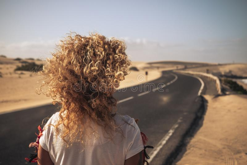 Back view of long blonde curly hair in the wind for freedom independence vacation concept - long asphalt beautiful road with. Desert dines and beach on the stock image