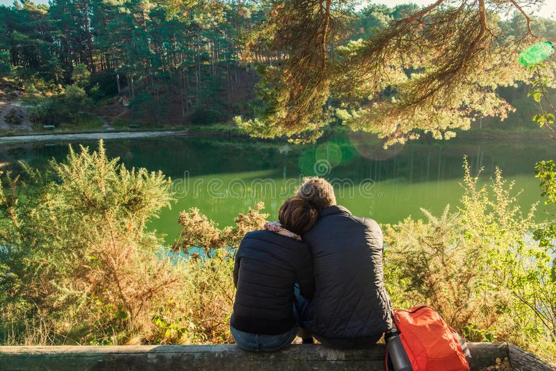 Back view of lovely couple man and woman sitting near forest lake hugging and relaxing. Love Emotions Outdoor concepts. Idyllic stock photo