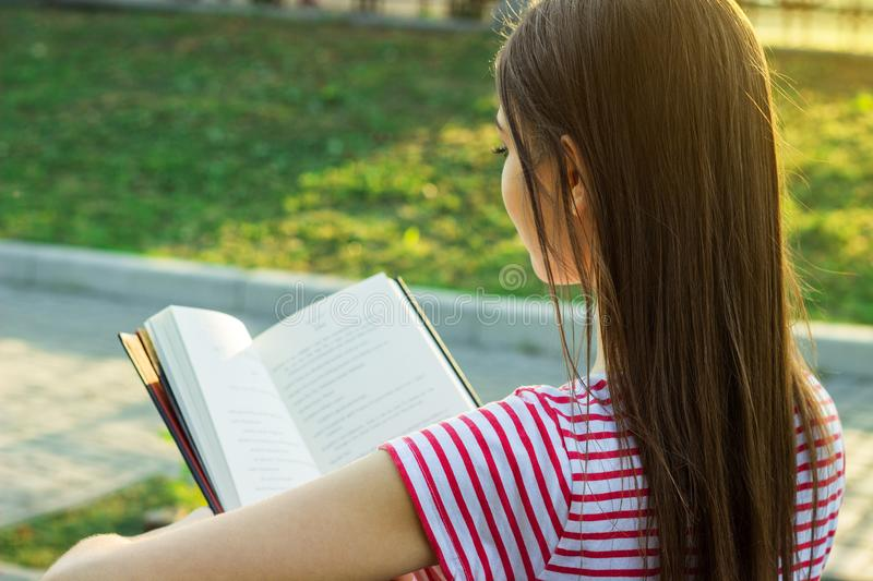 Back view of lovely young girl with long beautiful hair reading a book outside stock photography