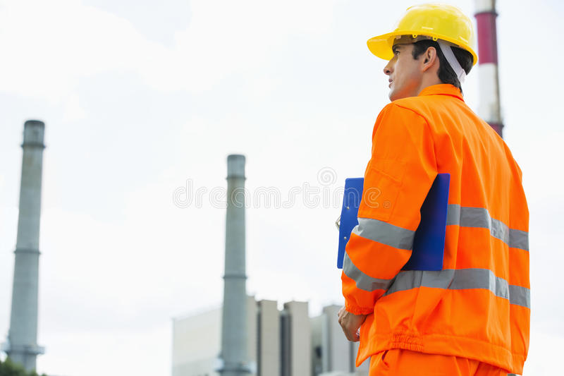 Back view of male architect with clipboard standing at site stock photography