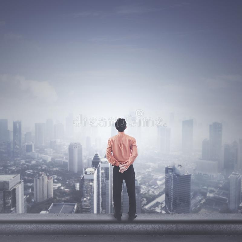 Male entrepreneur standing on the rooftop. Back view of male entrepreneur looking at a city while standing on the rooftop royalty free stock images