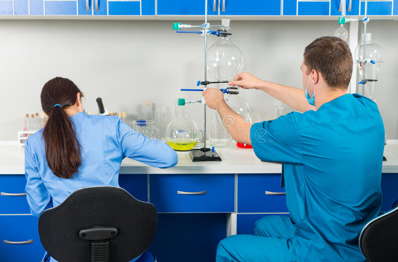 Back view of male and female scientists in uniform making some r. Esearches in a laboratory. Healthcare and biotechnology concept stock photos