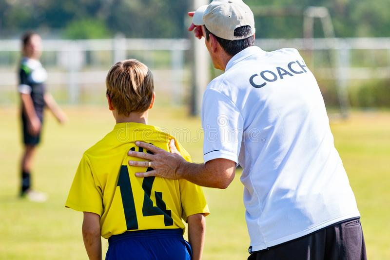 Back view of male football coach in white COACH shirt at an outdoor sport field sending his young boy player in the game stock photos