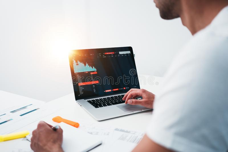 Back view of male manager sitting at desktop and monitoring statistics on monitor royalty free stock image