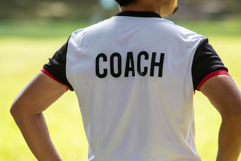 Back view of male soccer or football coach in white shirt with w stock photography