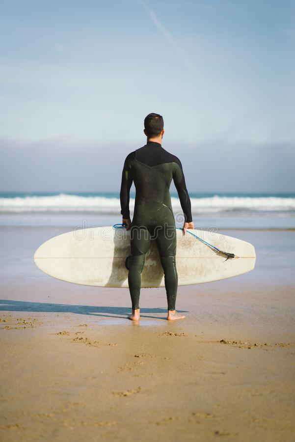 Surfer holding his surfboard towards the sea royalty free stock photo