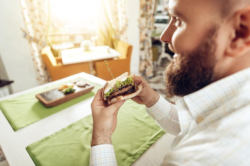 Back view man bite sandwich eating in cafe. A happy bearded man rejoices in a restaurant, consuming his food, which he ordered. The concept of restaurant royalty free stock images