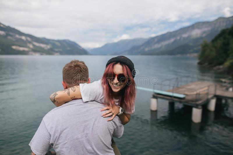 back view of man carrying happy young woman in sunglasses near majestic mountain lake royalty free stock photography