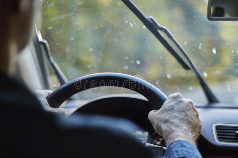 Back view of a man driving a car with moving windshield wipers during rain stock photos