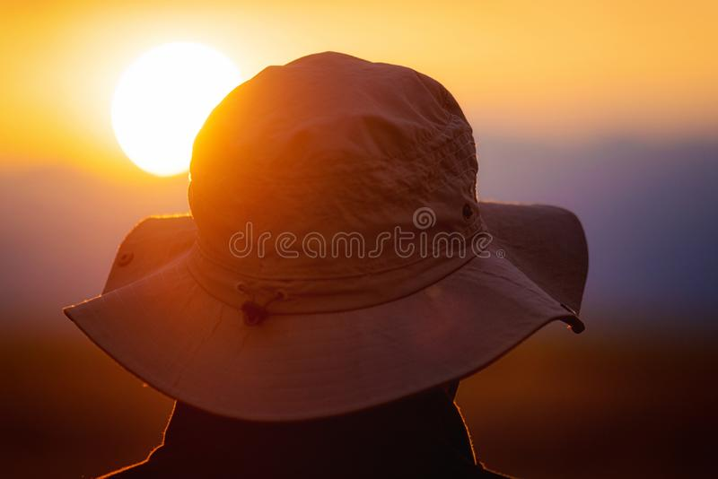 Back view of a man with explorer hat watching scenic sunset. Concept for travel exploration and discovery. Back view of a man with explorer hat watching scenic royalty free stock images