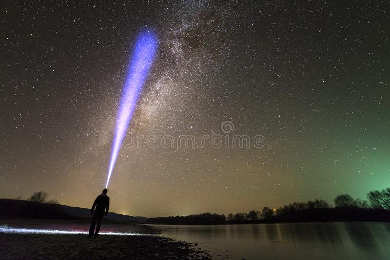 Back view of man with head flashlight standing on river bank, long blue beam across beautiful dark starry sky. Night photography. Concept. Wide panorama, copy royalty free stock images