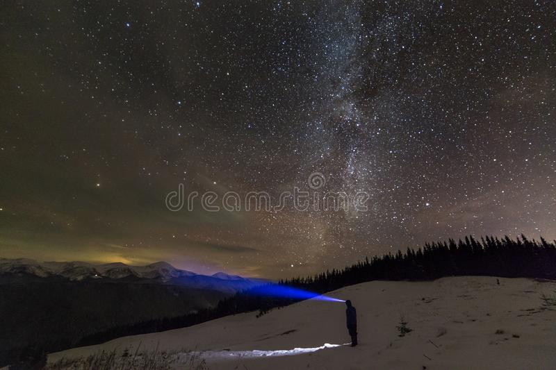 Back view of man with head flashlight standing on snowy valley under beautiful dark blue winter starry sky, bright blue beam on stock image