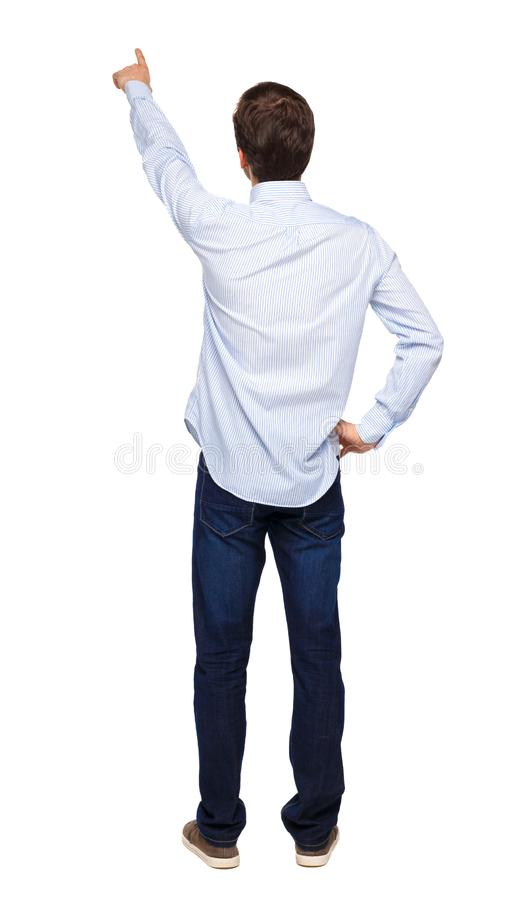 Back view of a man in jeans points his hand upwards royalty free stock photo