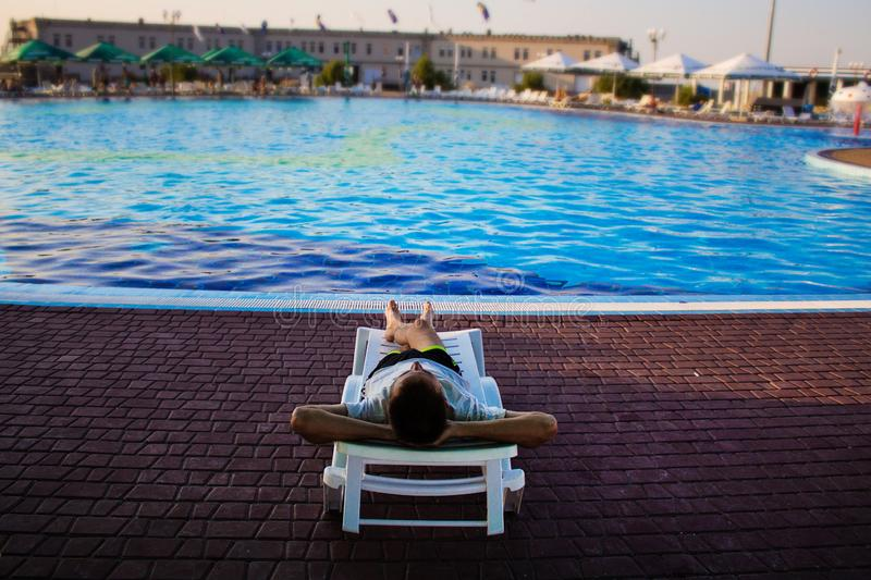 Back view of man lying on lounger near swimming pool at hotel, concept summer time stock photo