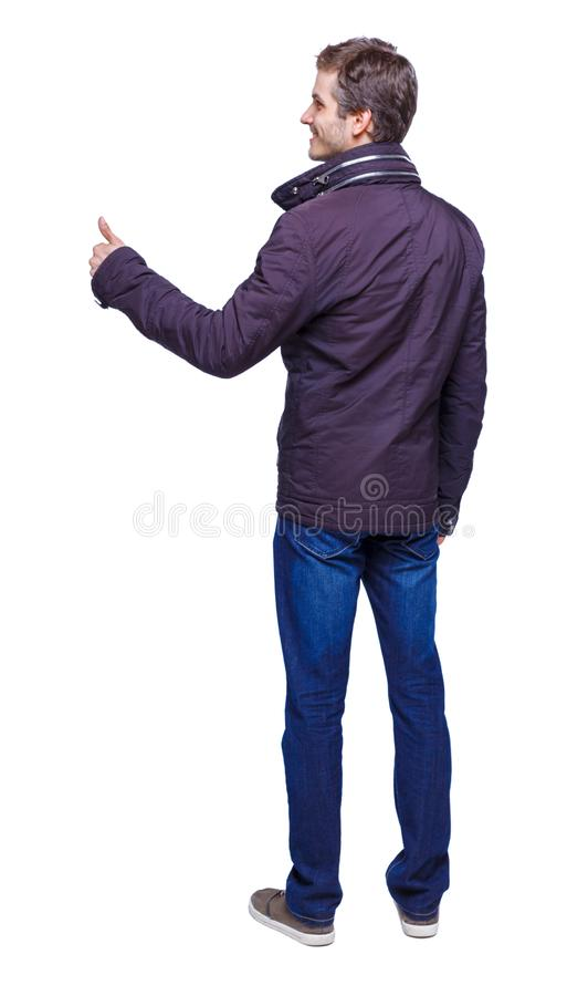 Back view of man in parka thumbs up stock image