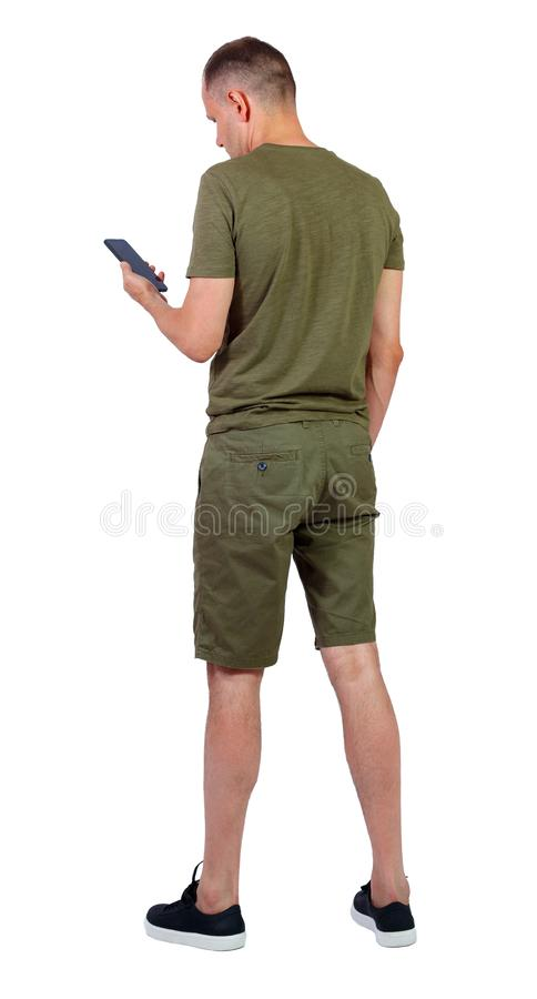 Back view of man in shorts who is looking into the smartphone royalty free stock image