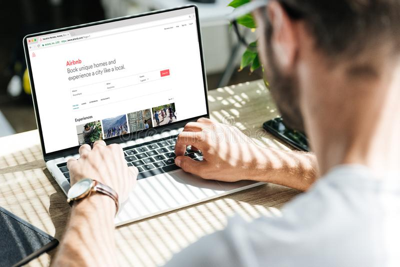 back view of man using laptop with airbnb website royalty free stock images