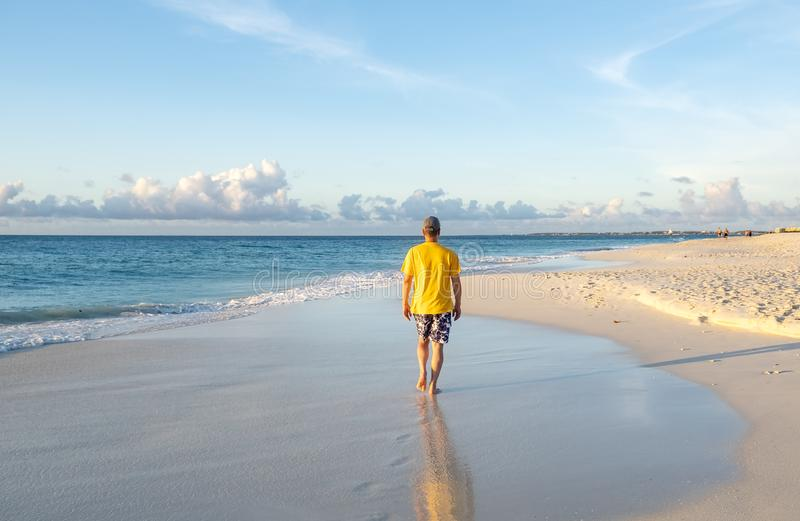 Back View of a Man Walking on a Caribbean Beach 2 stock image