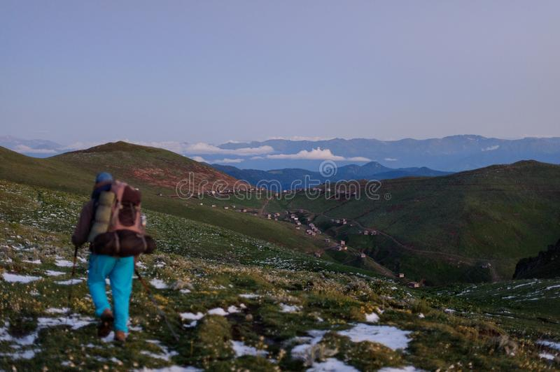 Back view man walking on the field with snow remnants with hiking backpack and sticks stock photo