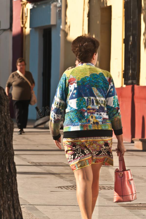 Woman dressed in colorful dress walking a street in old town Cadiz, Spain royalty free stock images