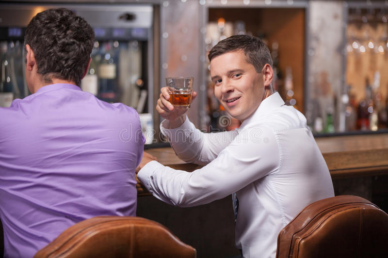 Back view of men sitting at counter. stock image