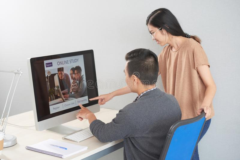 Colleagues discussing online study course at computer royalty free stock images