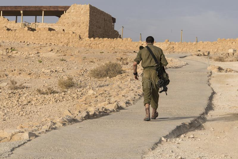 Back view of military going alone among deserted territory somewhere in the middle east. Masada fortification, Israel, war. Back view of a military going alone stock photos