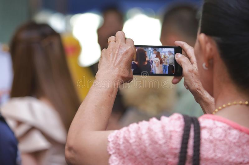 Back view of mobile smart phone is held against hands of senior Asian woman in luxury room background. Selective focus and shallow royalty free stock photo