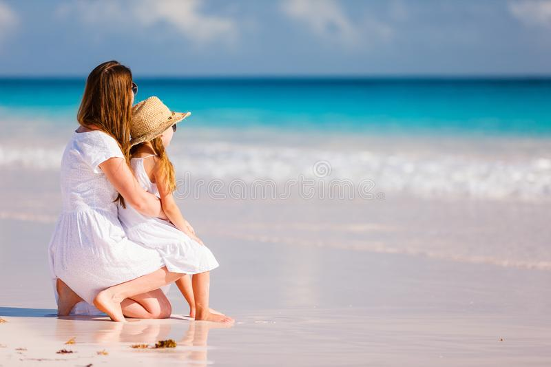 Mother and daughter at beach. Back view of mother and daughter at Caribbean beach royalty free stock photos