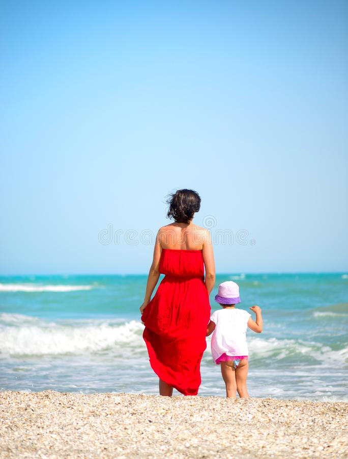 Mother with her little girl walking on the seashore royalty free stock images