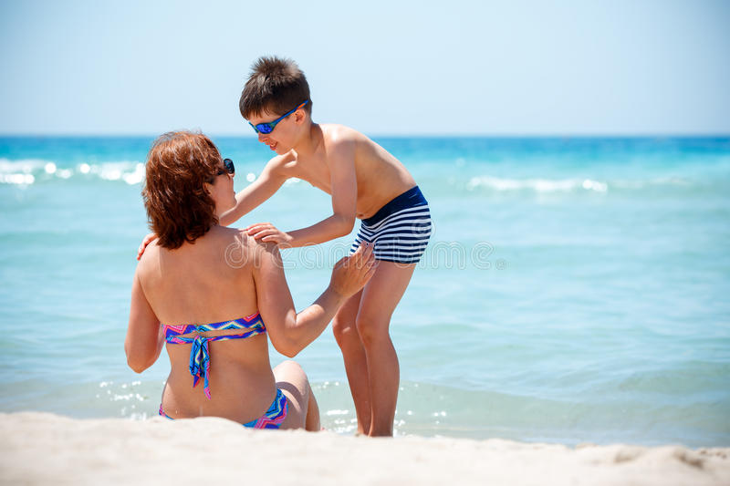 Back view of mother and son enjoying tropical beach vacation stock photos