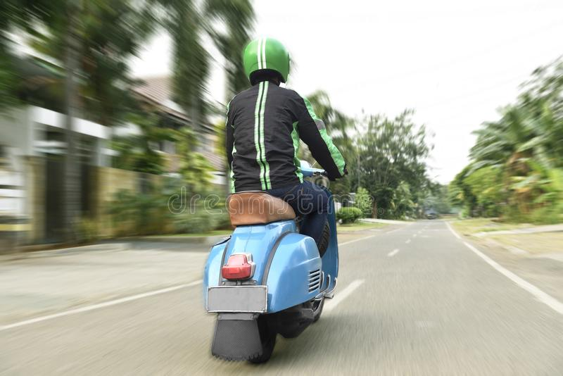 Back view of motorcycle taxi driver with blue scooter royalty free stock image