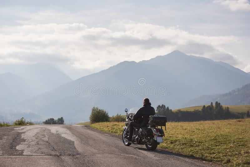 Biker in black leather outfit driving modern powerful motorcycle along sunny road on summer day. Back view of motorcycler in black leather jacket riding cruiser royalty free stock image
