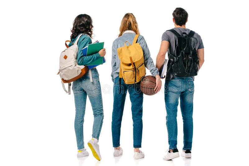 back view of multicultural students with backpacks and basketball ball stock photos